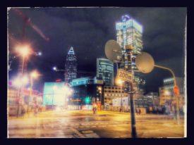 Stadtansicht. 4-teilige Kreuzung, Verkehrsschilder im Vordergrund, Passanten, im Hintergrund mehrere Hochhäuser, eines davon im Bau, mit Fotoeffekten verfremdet