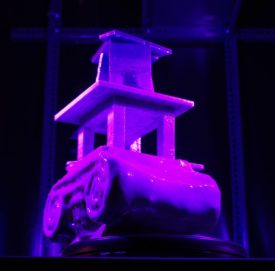 3D-Druck-Objekt. als Basis der Kopf einer anktiken Säule, darauf ein Konstrukt, in dem eine Wendeltreppe nach oben führt in eine Art Turm. auf einem Drehteller unter violettem und blauen Licht.