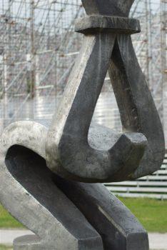 moderne Skulptur, die stilisiert eine kniende Person mit auf dem Rücken gefesselten und hochgerissenen Armen darstellt. das Bildformat reicht nicht ganz zur Darstellung aus.