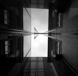 ein kleines Stück Himmel eingerahmt von Mauern. ein älteres Haus und daran angebaut ein Hochaus mit gläserner Fassade