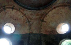 Altes Gewölbe von innen. Man sieht das alte Mauerwerk, teils mit Eisen armiert. links und rechts sind die Bögen von Ausgängen und darüber runden Fenstern, symmetrisch zur Bildmitte und durch das einfallende Licht sehr hell.