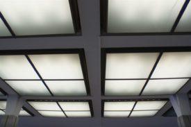 Blick zur Decke im Hauptbahnhof Kassel. Weiß gestrichene Decke, darin halb versenkt quadratische Lampen, die flächig weiß beleuchtet sind und in der Mitte von einem Kreuz geteilt werden wie ein Fenster.