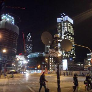 Stadtansicht. 4-teilige Kreuzung, Verkehrsschilder im Vordergrund, Passanten, im Hintergrund mehrere Hochhäuser, eines davon im Bau