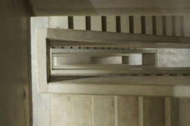 Ein Treppenhaus von oben. Die Treppe und das Geländer sind komplett aus blankem Beton, so wie er gegossen wurde, betont rauh belassen. Die Perspektive folgt der Lücke, um die sich die Treppe dreht. Im Bild sind vornehmlich der Handlauf und einige Stufen. Es ist nicht auf den ersten Blick zu erkennen, dass es ein Treppenhaus ist, wegen der ungewohnten Perspektive.
