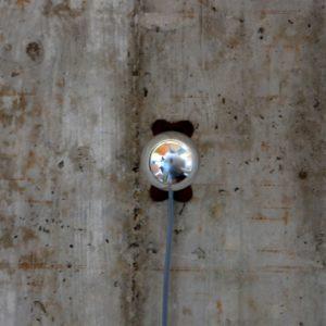 Glühbirne an einer rauhen Betondecke. die Birne ist zentral in der Bildmitte, könnte auch an der Wand oder am Boden angebracht sein, das geht aus dem Bild nicht hervor. von unten zur Birne führt ein blaugraues Kabel. Die Birne selbst ist verspiegelt, von ihr zu sehen ist nur eine spiegelnde Kuppel, in ihr spiegelt sich verzerrt der Raum.